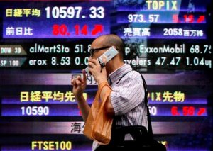 A man talks on his cell phone past the electronic stock board of a securities firm in Tokyo, Japan, Friday, Aug. 14, 2009. Japan's Nikkei 225 stock average rose 80.14 points, or 0.8 percent, at 10,597.33, the highest close since Oct. 3. (AP Photo/Itsuo Inouye)